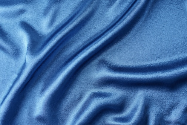 Blue silk background with folds.  abstract texture of rippled satin surface