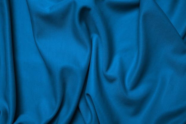 青い絹の折り畳まれた生地の背景