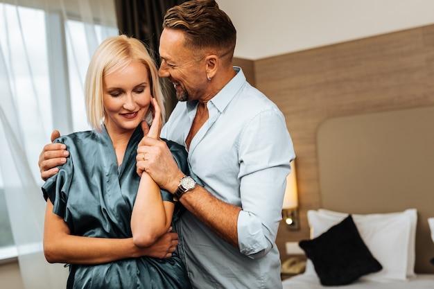Белье из шелка синего цвета. улыбающийся человек в белой рубашке нежно обнимает свою хорошо одетую блондинку-любовника
