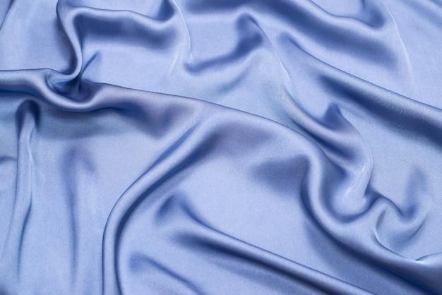 Синяя шелковая или атласная текстура роскошной ткани. вид сверху.