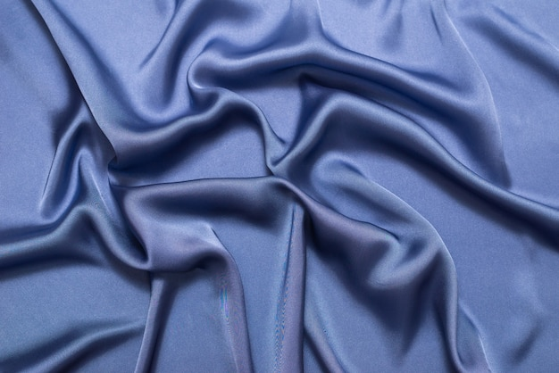 Синий шелк или атласная роскошная ткань текстуры. вид сверху.