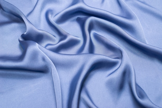 Blue silk or satin luxury fabric texture. top view.