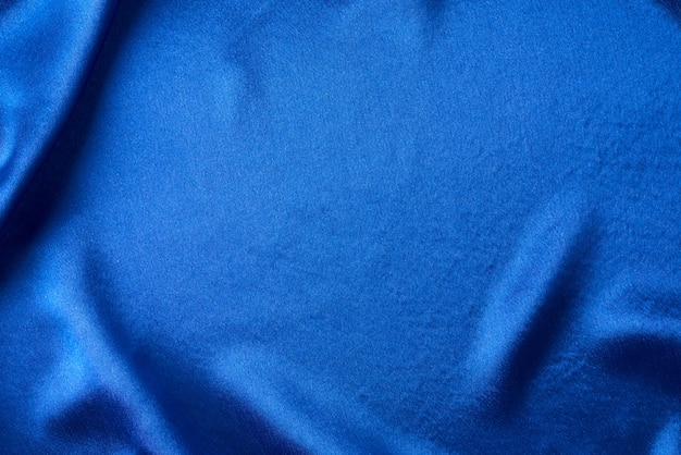 Blue silk with folds.  abstract texture of rippled satin surface