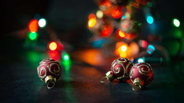 Blue and silver christmas ball on dark garland illuminated background.