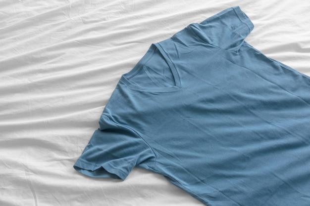 青いシンプルなtシャツは白いシーツの上にあります。