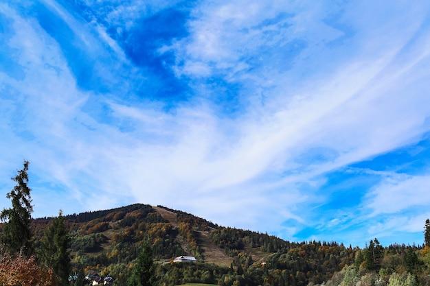 山の上の青い空、木々に覆われています。巻層雲。