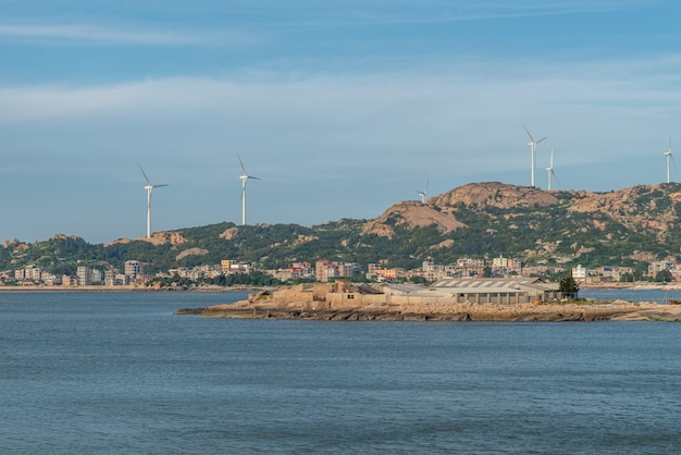 Under the blue sky, across the sea are mountains and wind power