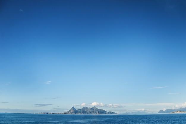 푸른 하늘과 멀리있는 섬. helligvaer는 노르웨이 nordland 카운티의 bodo시의 vestfjorden에있는 섬 그룹입니다.
