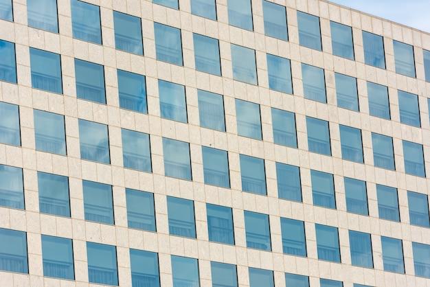 현대 오피스 빌딩의 창문에 반사된 푸른 하늘과 구름