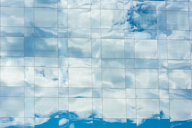 近代的なオフィスビルの窓に映る青い空と雲