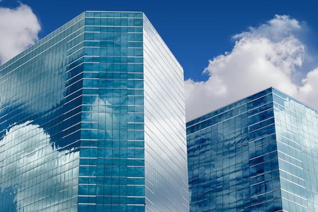 Голубое небо и облака, отражающие в окнах современного офисного здания