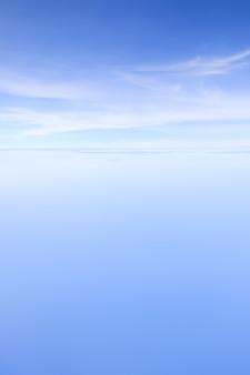 地上から約25000フィートの高さの飛行機の窓から取られた青い空とクラウンド