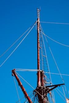 Голубое небо и мачта старого парусного корабля в морском порту