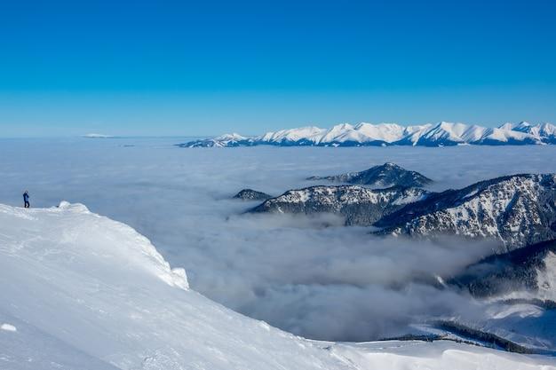 雪に覆われた山頂の青い空と晴天。谷は濃い霧です。孤独な観光客が美しさを写真に収める