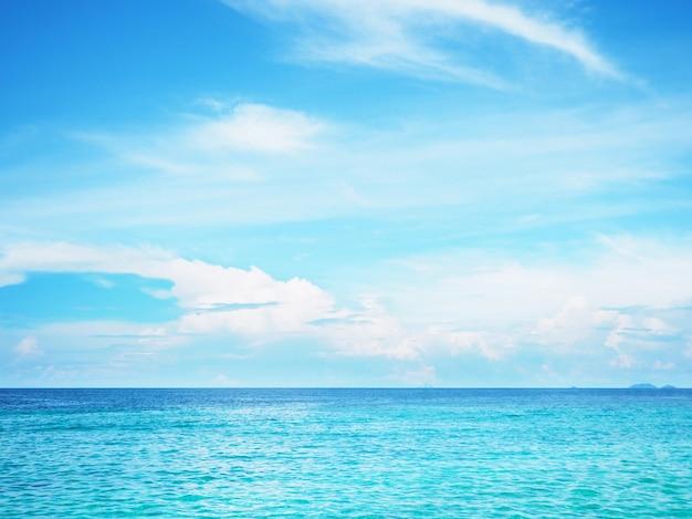 青い海の表面上の青い空と白い雲