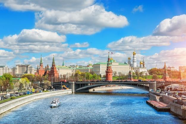 Голубое небо и белые облака над московским кремлем и прогулочный катер