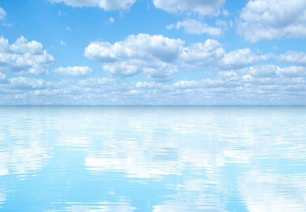 Голубое небо и белые облака отражаются в морской воде.