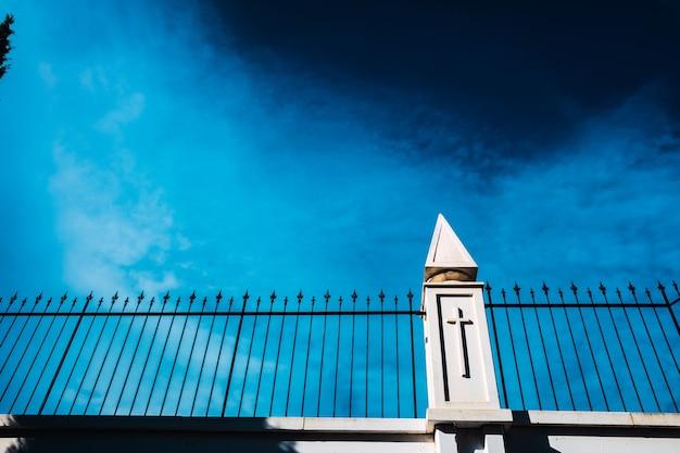 Голубое небо за белой стеной с забором с религиозным крестом