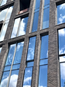푸른 하늘은 현대 로프트 건물의 창 창에 반영됩니다