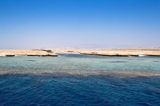 日光の反射と穏やかな海の上の青い空
