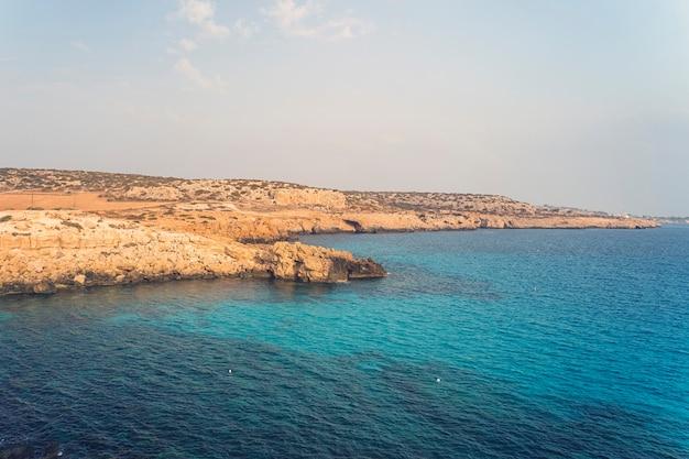 Blue sky. sea rocks and rocks on the beach of aphrodite. cyprus. mediterranean sea