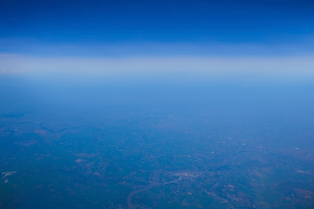 Blue sky and white clouds with land from top view on air plain