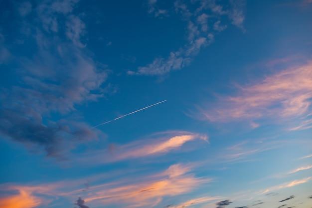雲と空中の高い飛行機のある青い空は、日没または日の出に広く目的地に飛んで、後ろに白い縞模様を残します