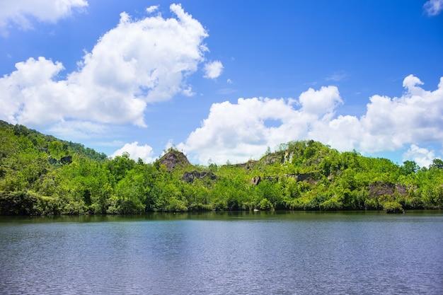 Голубое небо с облаками, гора, покрытая множеством деревьев, и озеро перед ними.