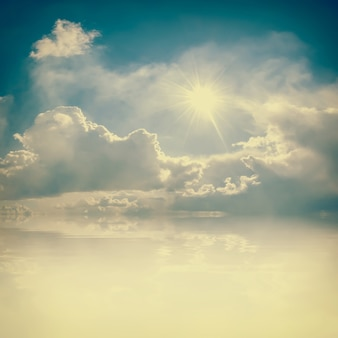 Blue sky with clouds and sun, place for your text
