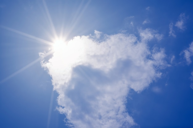 Blue sky with clouds and sun reflection. the sun shines bright in the daytime in summer