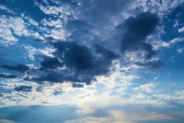 해질녘 구름 아래에서 어둡고 흰 구름과 태양 광선이 있는 푸른 하늘