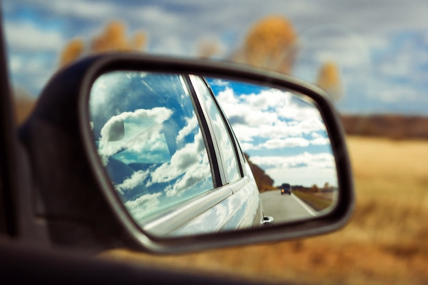 Blue sky with fluffy clouds and road reflection an car mirror on a background of autumn field