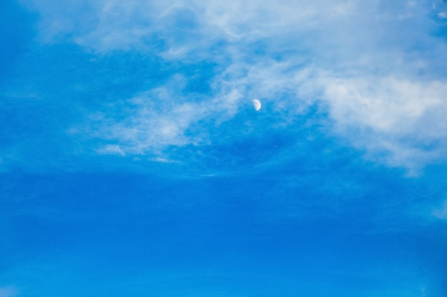 Blue sky with moon and white clouds in the evening