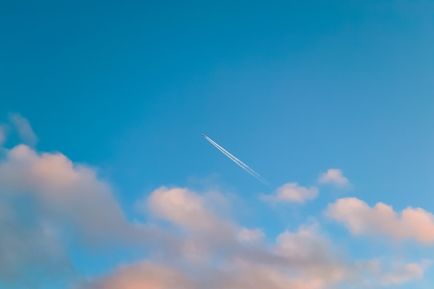Blue sky with pink clouds and airplane trail.