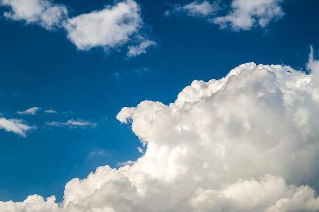 Голубое небо с пухлыми белыми облаками в яркий ясный солнечный день