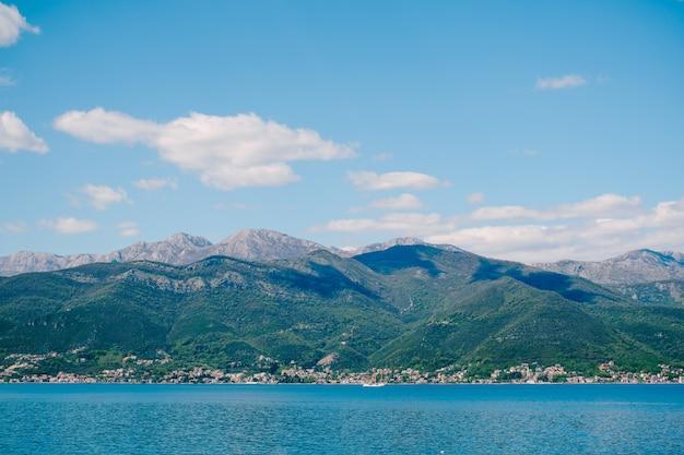 Голубое небо с белоснежными облаками над которским заливом в черногории