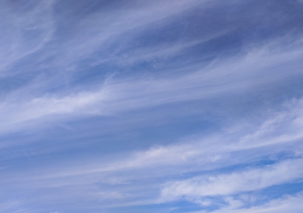 Blue sky with stripped clouds long transparent cloudscape sunny summer day background