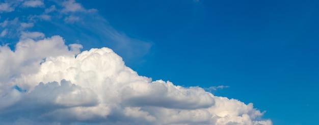 대각선으로 배열 된 흰 곱슬 구름과 푸른 하늘