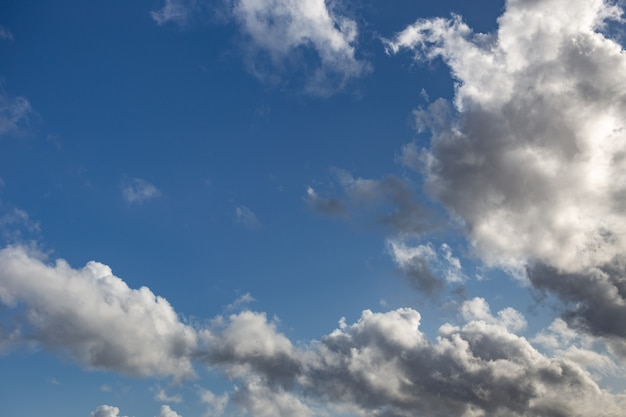 Blue sky with white and dark clouds background