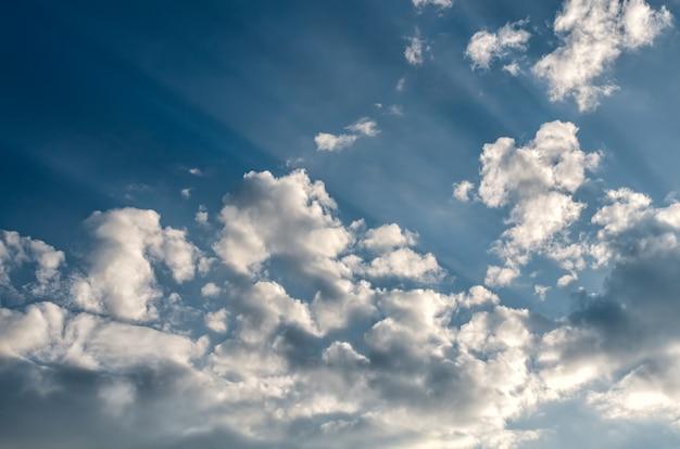白いふわふわの雲と太陽光線と青い空