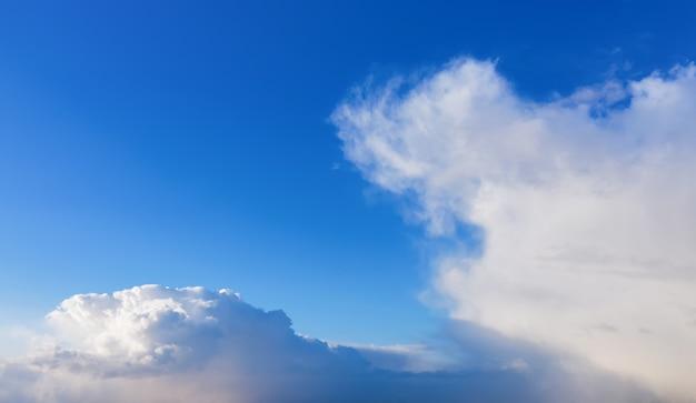 日光の下で白いふわふわの雲と青い空。自然な背景。