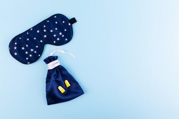 青い睡眠マスクと青色の背景に耳栓