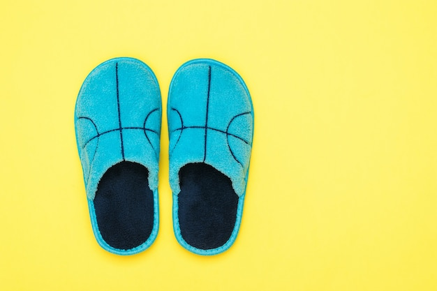 Blue slippers on bright yellow. comfortable home shoes. flat lay.