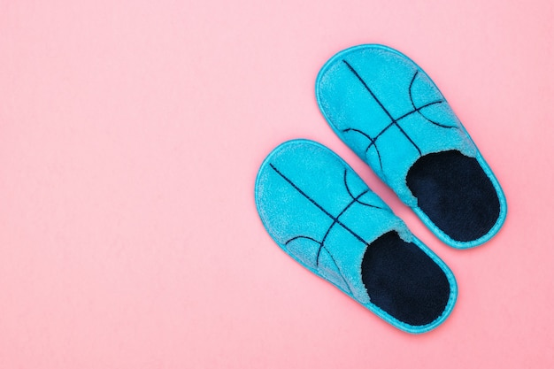 Blue slippers on a pastel pink surface