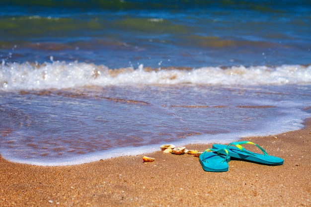 Blue slippers stand on the sand on the seashore.