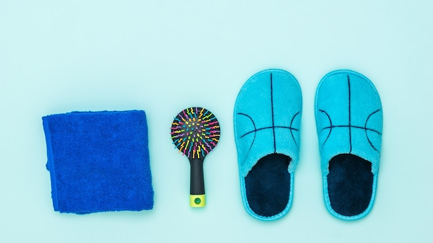 Blue slippers, towel and comb on blue background. set of morning accessories.