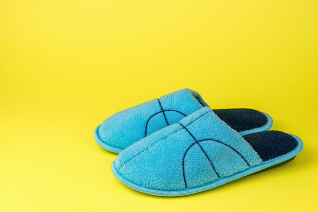 Blue slippers with embroidery on a yellow surface