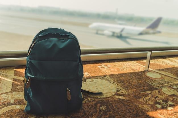 Синий небольшой рюкзак, стоящий на полу в аэропорту на фоне летящих и приземляющихся самолетов. отравленный синий рюкзак на полу. забытый багаж. потерянная ручная кладь.