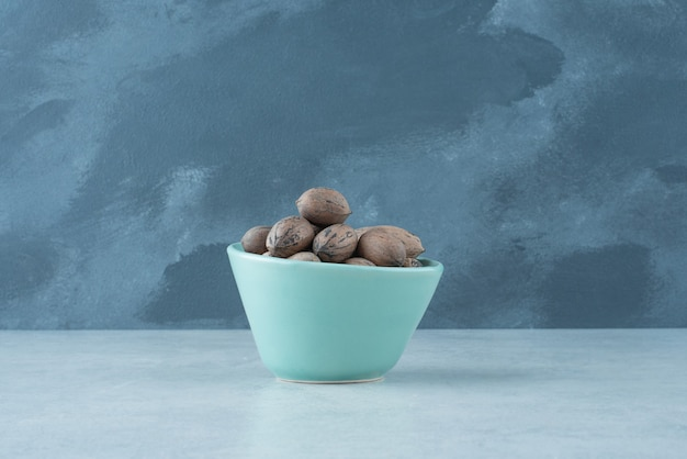 A blue small plate full of nuts on marble background. high quality photo