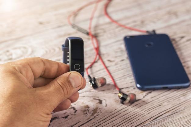 手に青いスマートブレスレットと木製のテーブルに青いスマートフォンと赤いヘッドフォン
